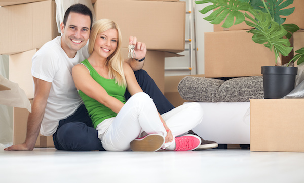 Happy young couple with boxes and keys to house