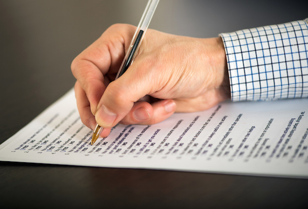 Close up fo the hand of a man completing a questionnaire