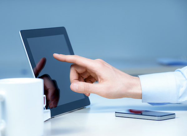 Hand pointing on modern digital tablet pc at the workplace.