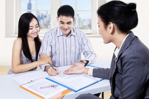 Young couple signing for financial contract with businesswoman